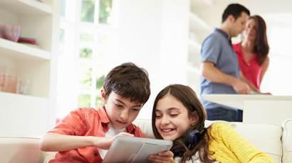 Frère et soeur jouant sur tablette tandis que les parents préparent le diner