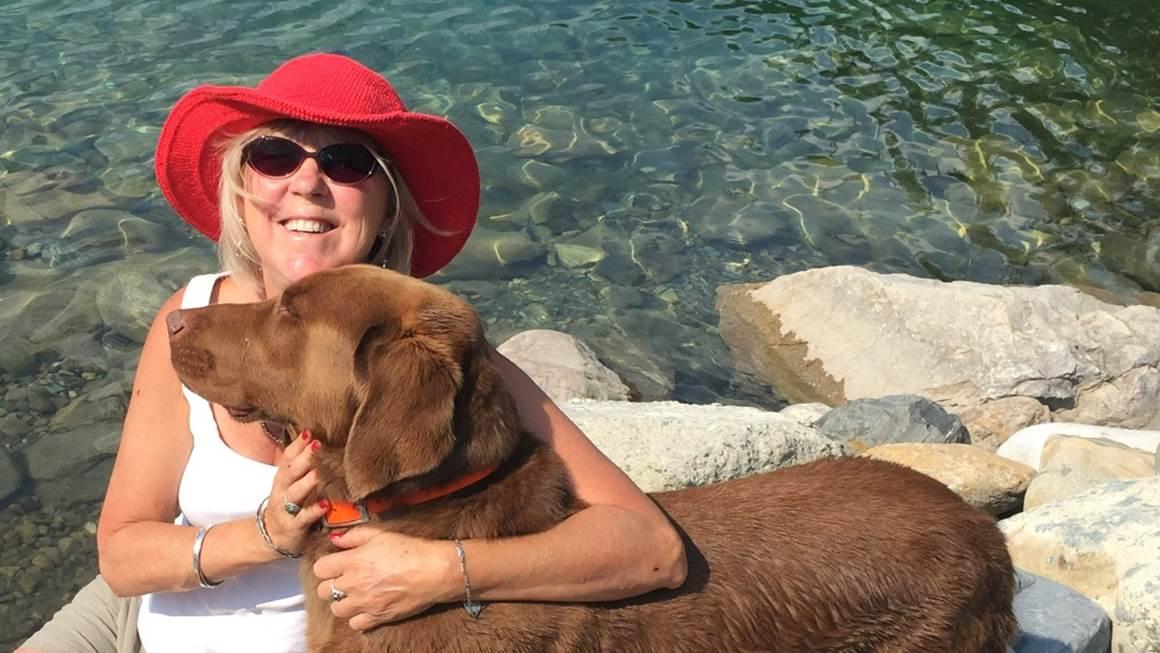 Sandra Thornton hugs her dog by a lake.