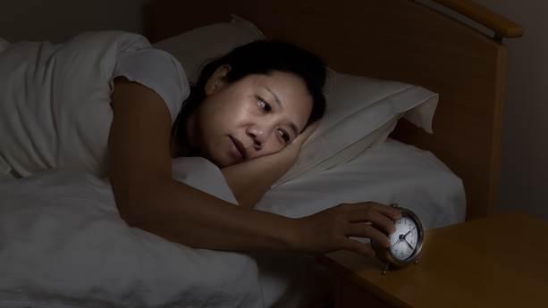 Une femme avec insomnia touche un réveil