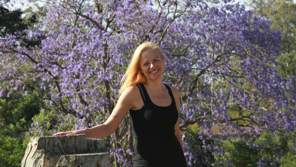 Annie Richard se tenant debout devant un arbre à fleurs pourpres