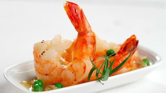 Crevettes cuites et petits pois servis sur assiette blanche