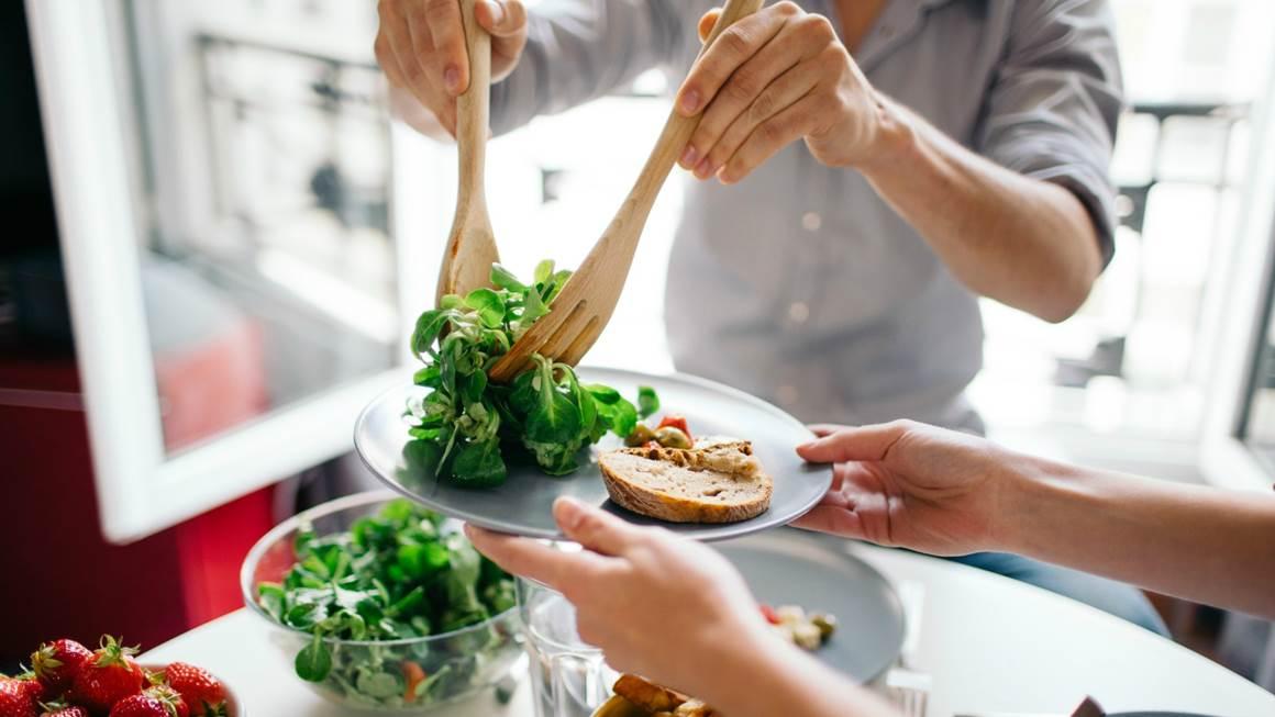 Un homme sert de la salade sur une assiette blanche avec du pain.