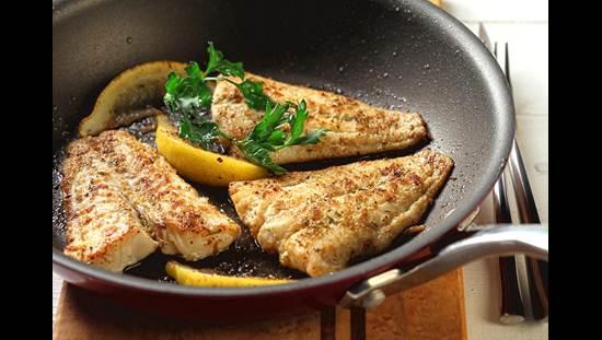 Trois morceaux de poisson cuit au poivre avec du citron et des herbes