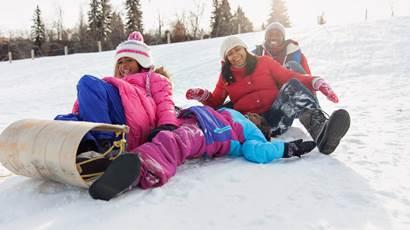 Famille faisant de la luge sur une colline enneigée