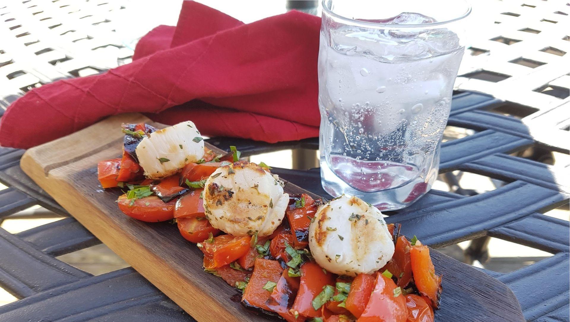Pétoncles grillés aux tomates rôties sur une planche de bois