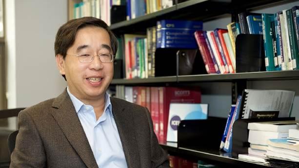 Dr Jack Tu devant une étagère