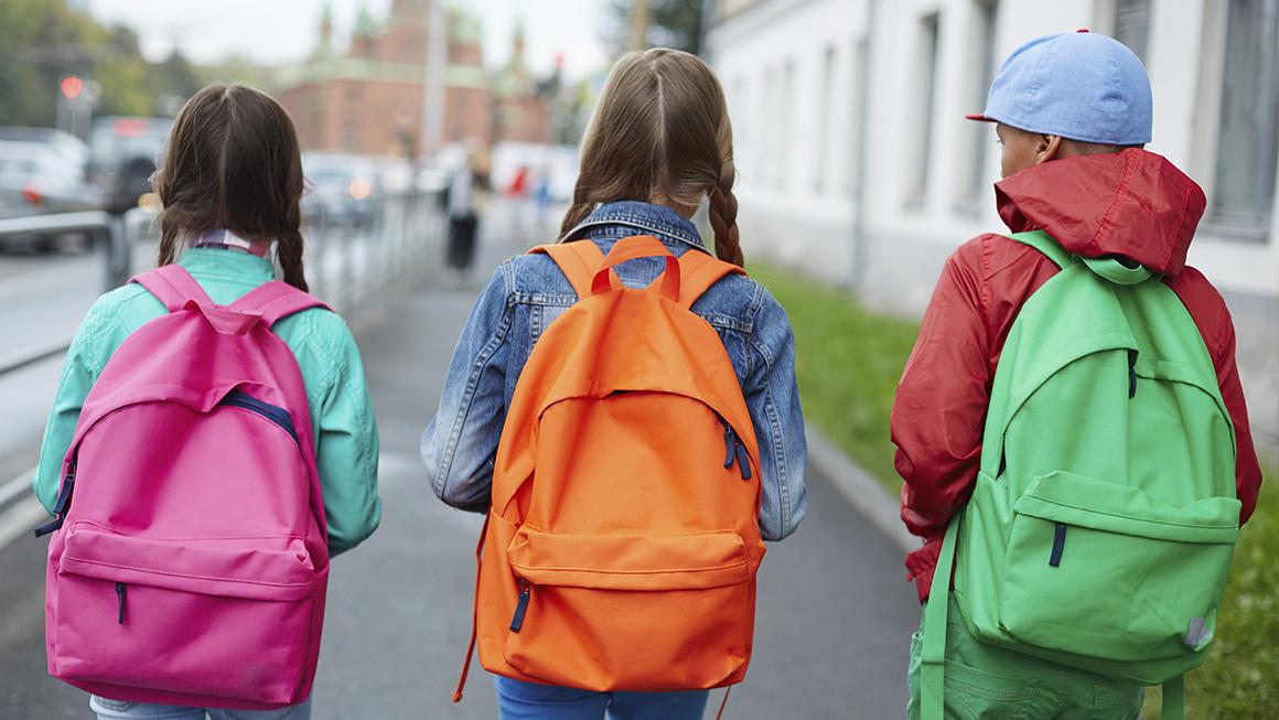 Trois enfants avec des sacs à dos marchent pour aller à l'école.