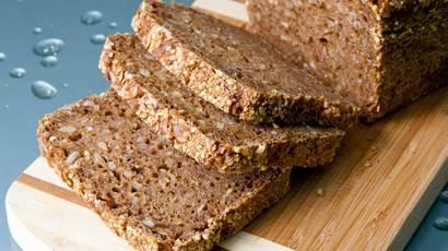 Miche de pain de grains entiers et les tranches sur une planche à découper en bois