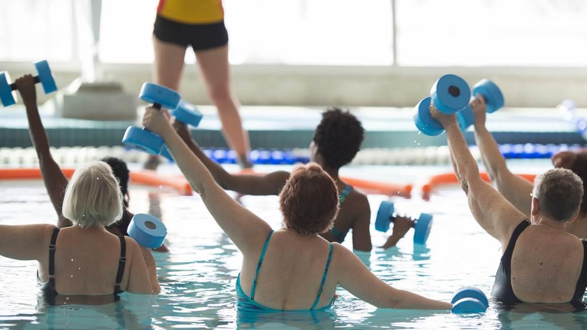Un groupe de femmes âgées exercent dans une piscine.