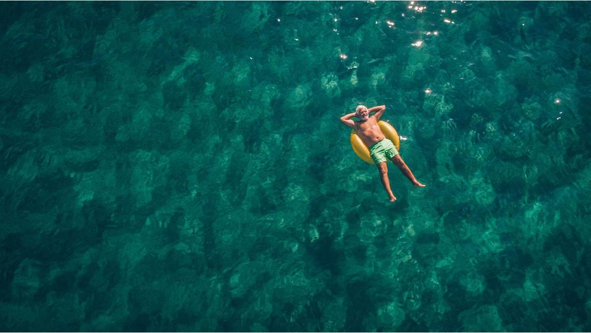 Homme posé sur anneau de natation dans la mer