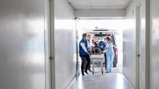 Une équipe médicale pousse un patient sur une civière dans un hôpital.
