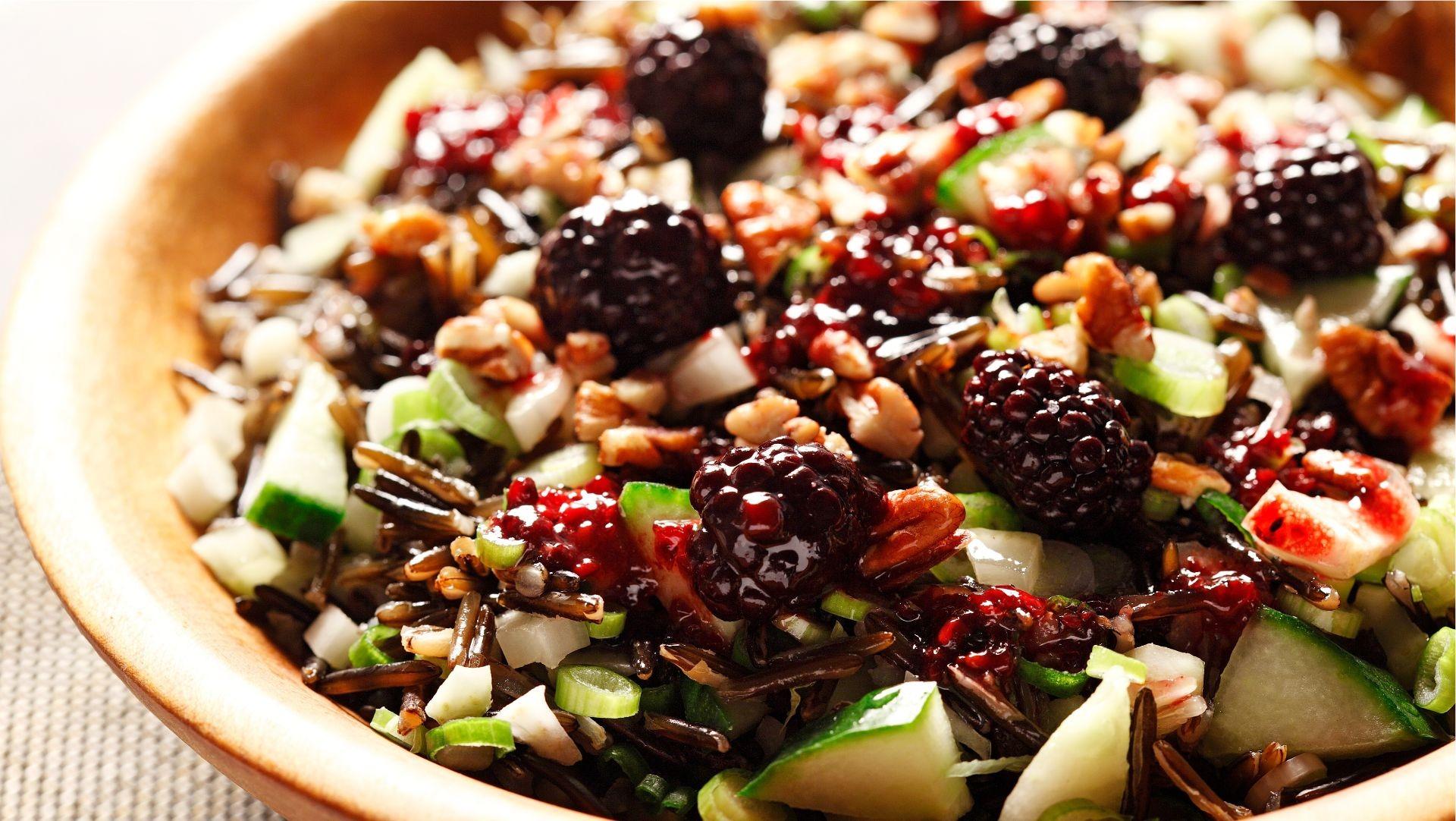 Salade croustillante de riz sauvage avec vinaigrette de mûre dans un bol de bois.