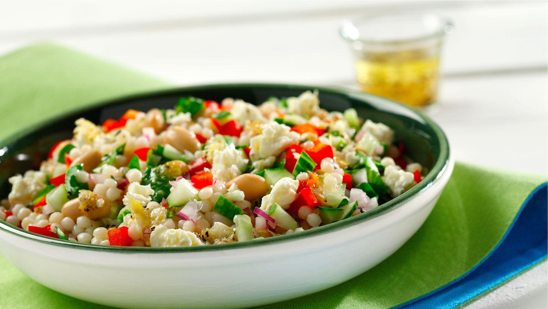 Salade de couscous perlé avec feta et romarin dans un bol blanc sur un set de table vert.