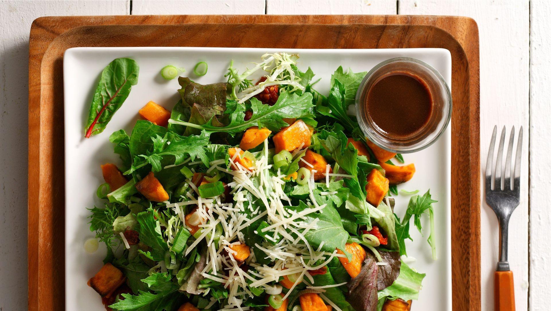 Salade tiède de patates douces, tomates séchées et roquette sur un plat blanc carré.