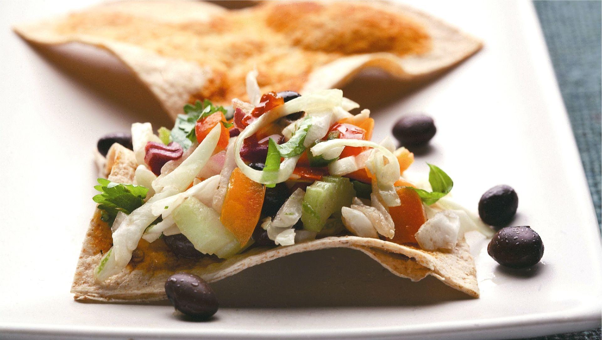 Salade de chou avec tortillas de blé entier triangulaires sur une assiette blanche.