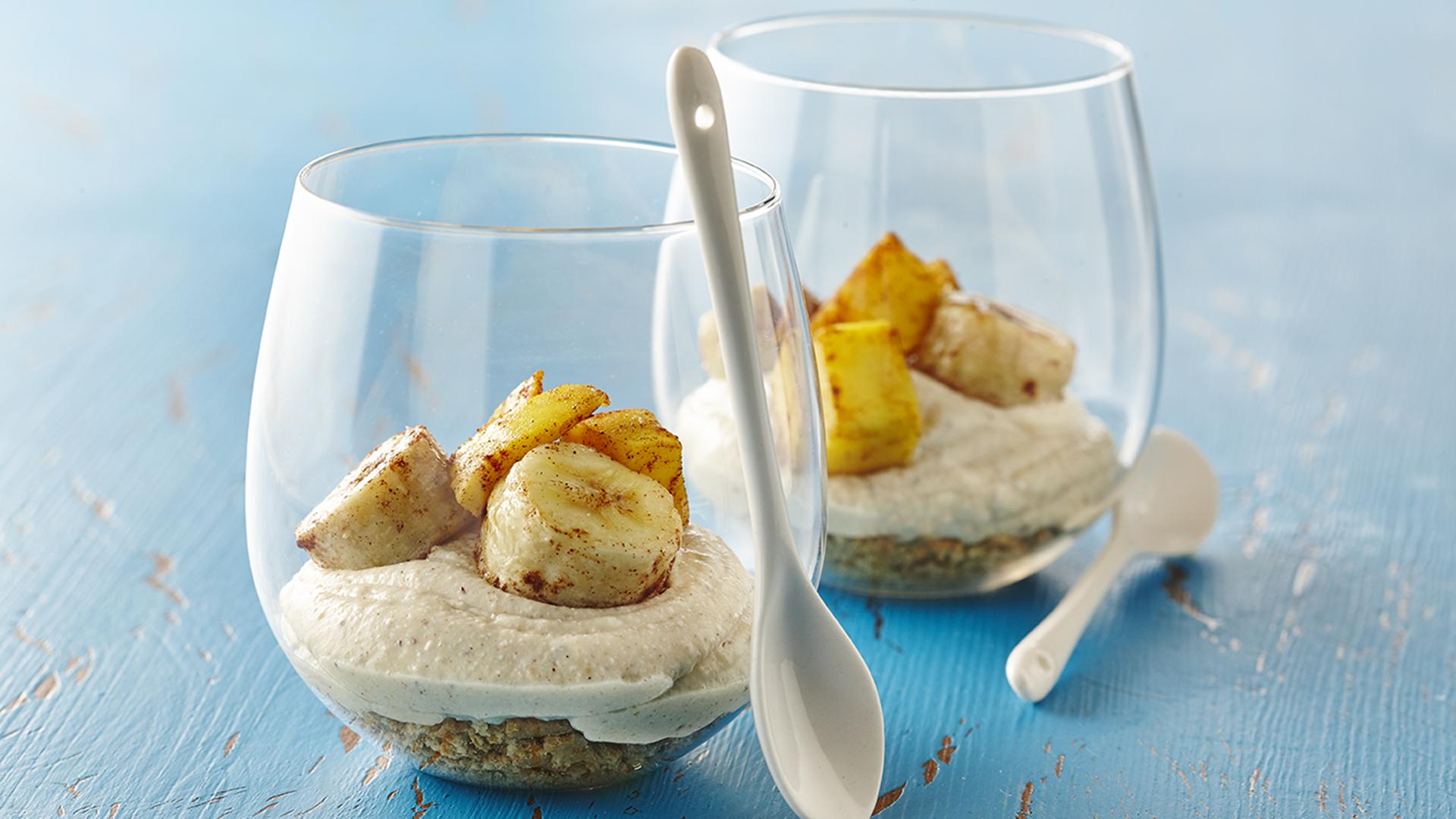 Deux verres remplis de gâteau au fromage, de bananes et de mangue rôties