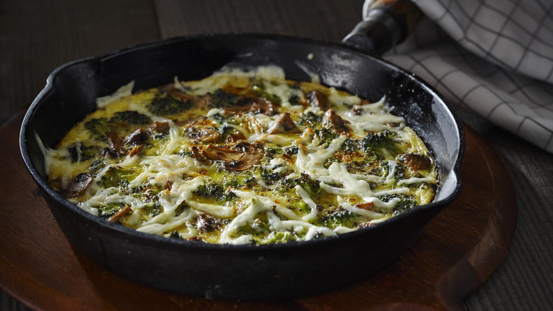 Frittata de brocoli et de champignons avec mozzarella râpée dans une poêle