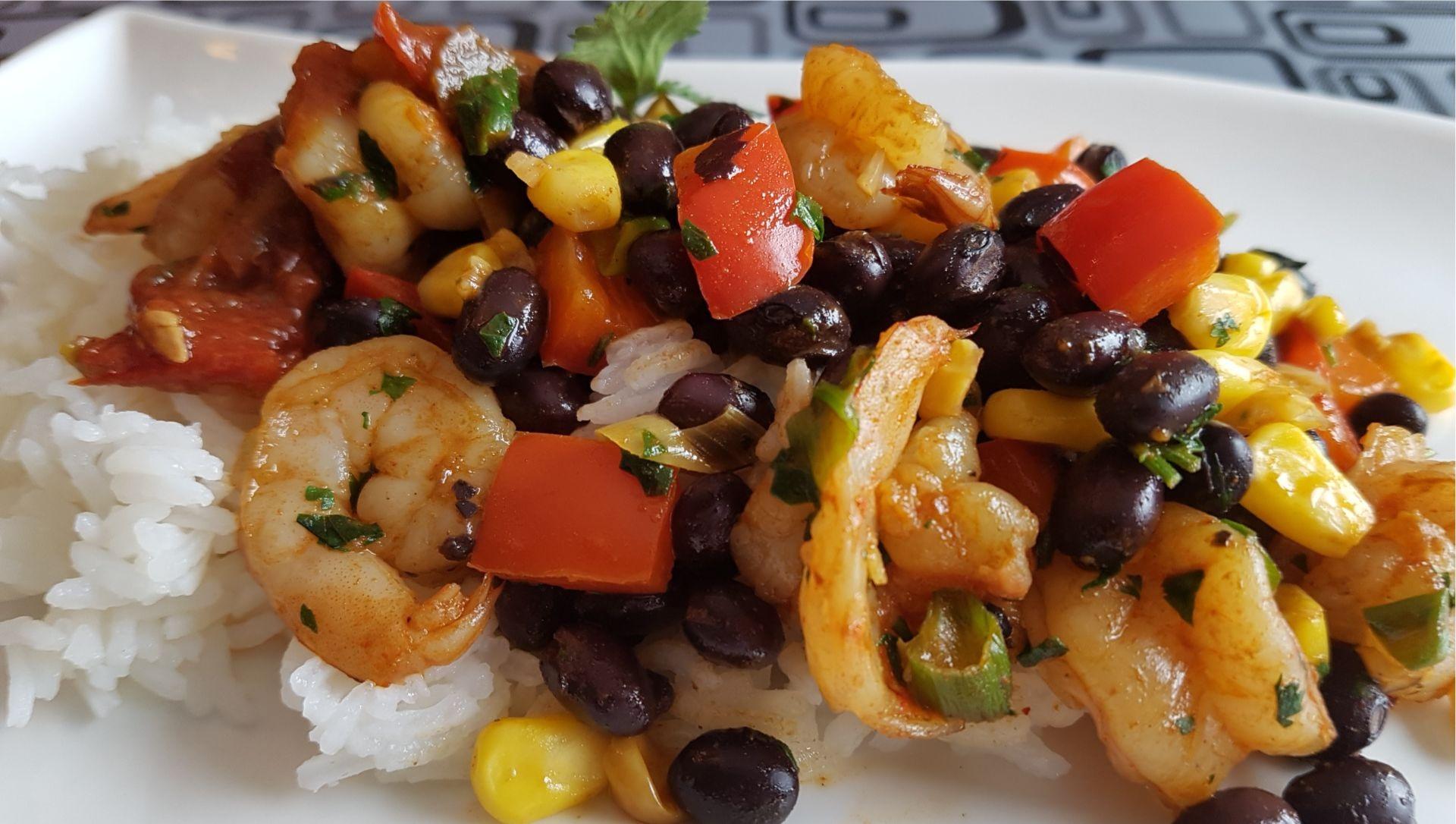 Crevettes, poivrons rouges, haricots noirs, maïs, riz blanc sur plaque