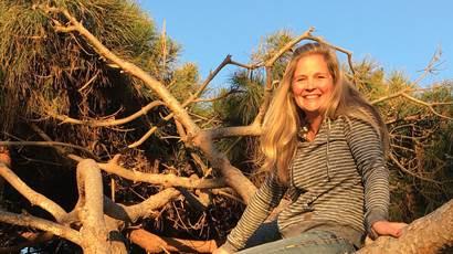 Wendy Swain sourit devant un arbre tropical.