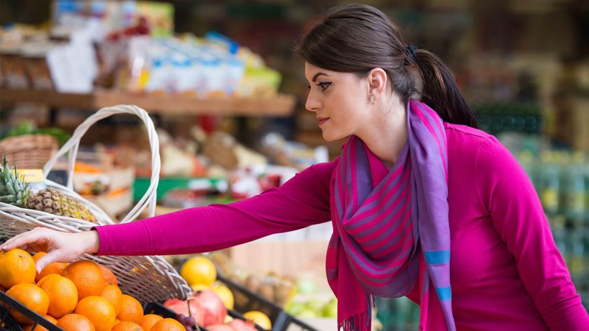 Femme, achat, oranges dans un supermarché