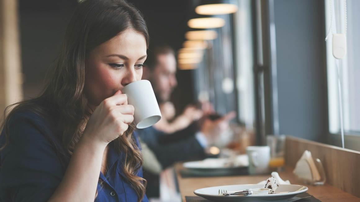 Une femme assise dans un restaurant sirote un café dans une tasse blanche.