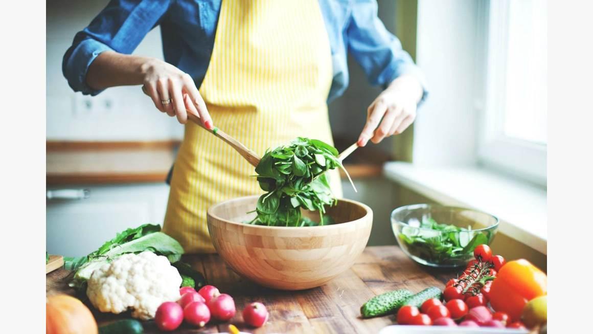 Une femme qui porte un tablier jaune remue une salade verte dans un bol en bois.