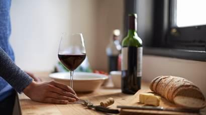 Une femme appuyée sur un comptoir de cuisine, devant une coupe de vin rouge, du pain et du fromage