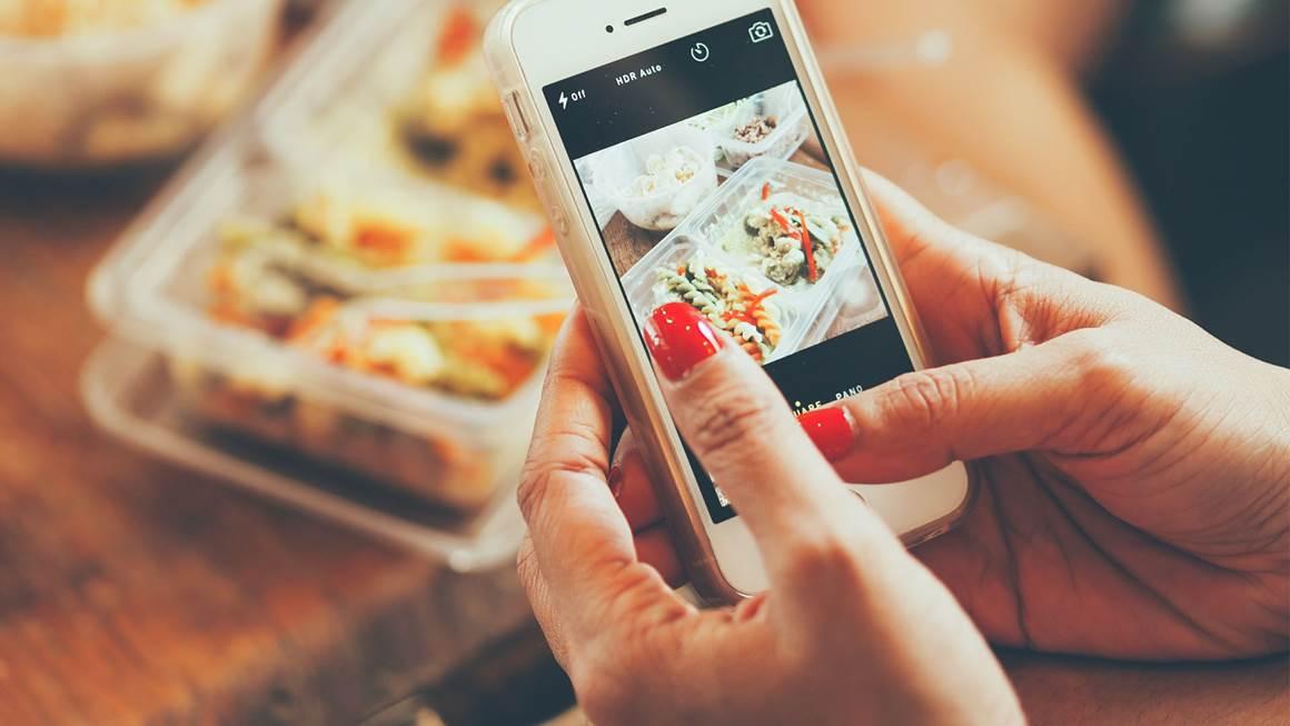 Femme de photographier la nourriture avec un téléphone