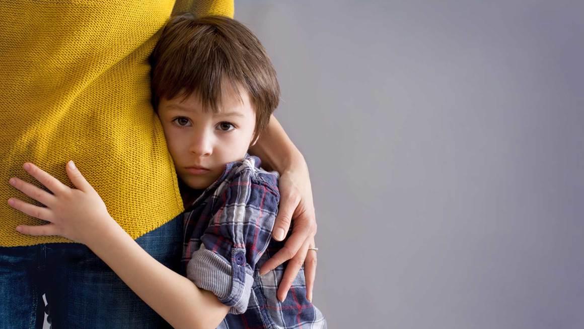 Triste petit enfant, garçon, étreindre sa mère à la maison