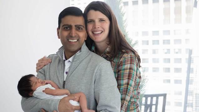 Irfhan Rawji et sa conjointe Christine sourient alors quIrfhan berce leur fils
