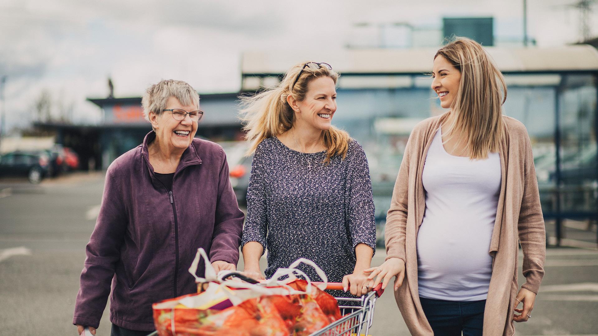 Une femme d'âge mûr, une femme d'âge moyen et une femme enceinte qui font les courses