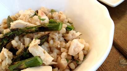 Salade de poulet à l'orge et aux asperges sur un plat blanc et un bol blanc