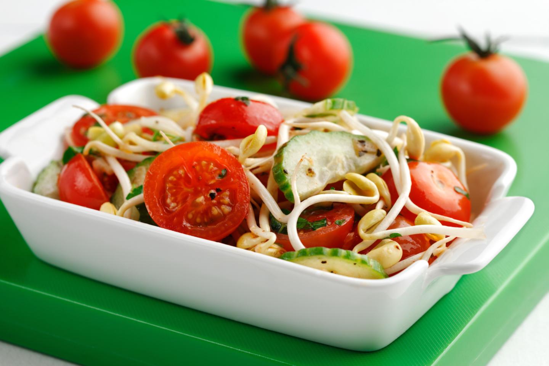Salade de tomates et fèves germées dans un plat blanc sur une planche verte