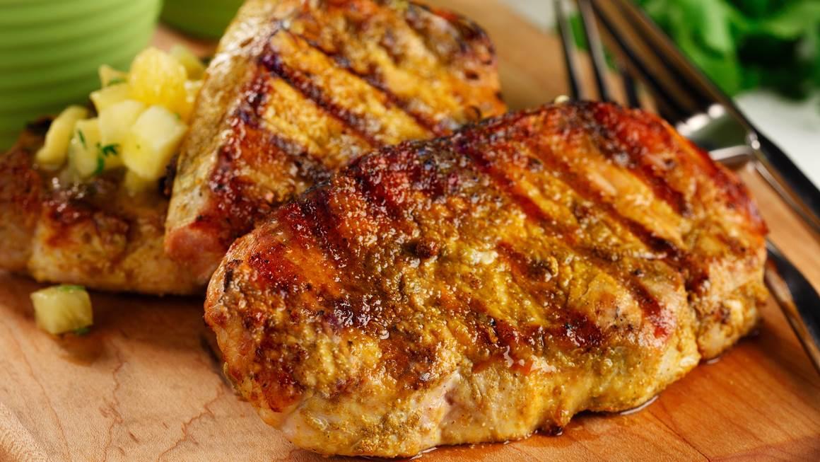 Gros plan des côtelettes de porc grillées sur une planche à découper l