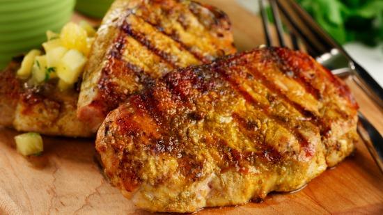 Gros plan des côtelettes de porc grillées sur une planche à découper l' ananas