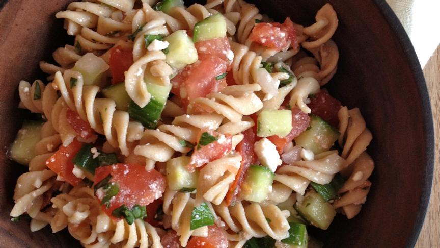 Salade de pâtes au gaspacho de tomate et concombre en gros morceaux dans un bol de bois