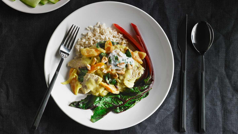 Cari de porc au gingembre avec carottes et légumes verts sur une assiette blanche, sur une nappe en lin gris