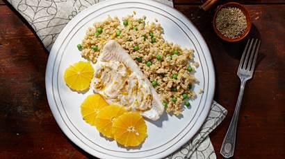 Poisson marocain épicé et couscous sur une assiette blanche avec tranches d'orange