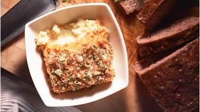 Purée de pommes de terres deux couleurs dans un plat carré blanc avec un couteau et du pain