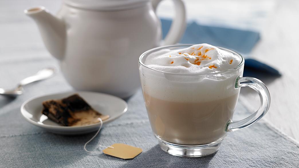 London Fog parfumé à l'orange dans une tasse claire, sur une assiette blanche et un pot de thé blanc au fond