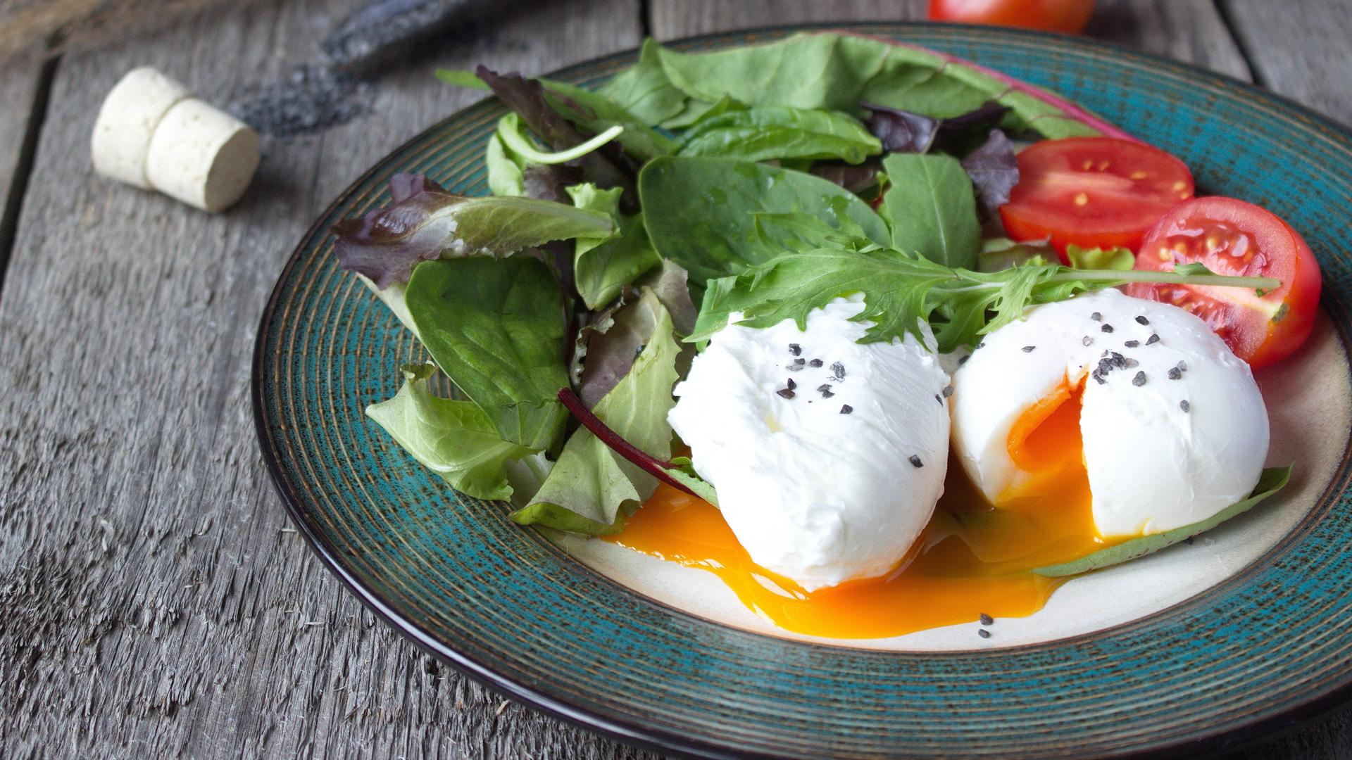 Oeufs pochés sur la plaque avec salade verte et tomates