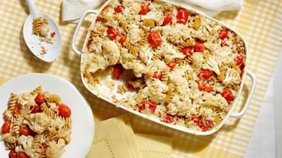 tomate asado y coliflor horneado de pasta en una cacerola rectangular de color blanco sobre un fondo blanco y amarillo