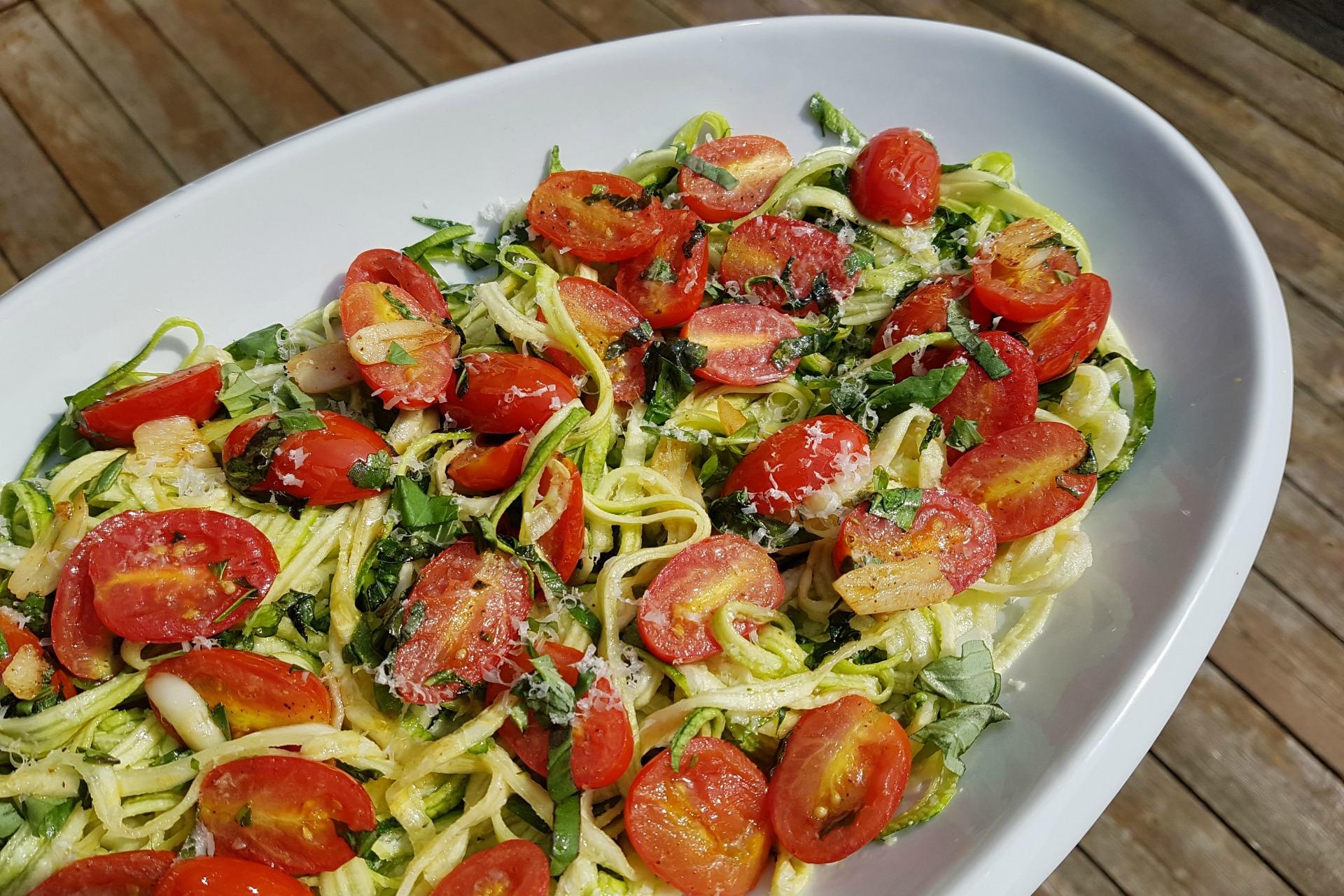 Assiette de nouilles courgette en spirale, tomates et basilic