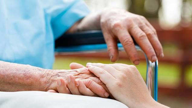 Docteur tenant patients âgé main dans un fauteuil roulant