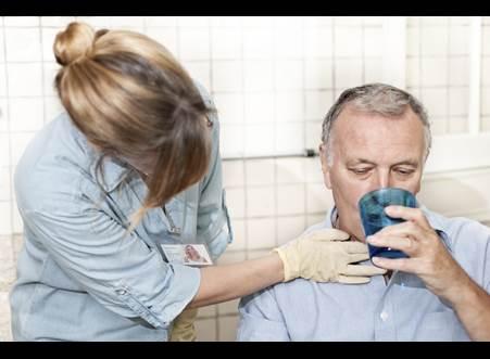 Un homme boit de l'eau dans une tasse à l'aide d'une infirmière.