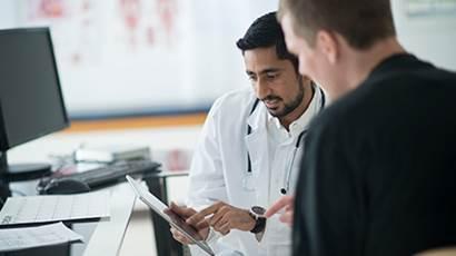 Un médecin et un patient regardent une tablette
