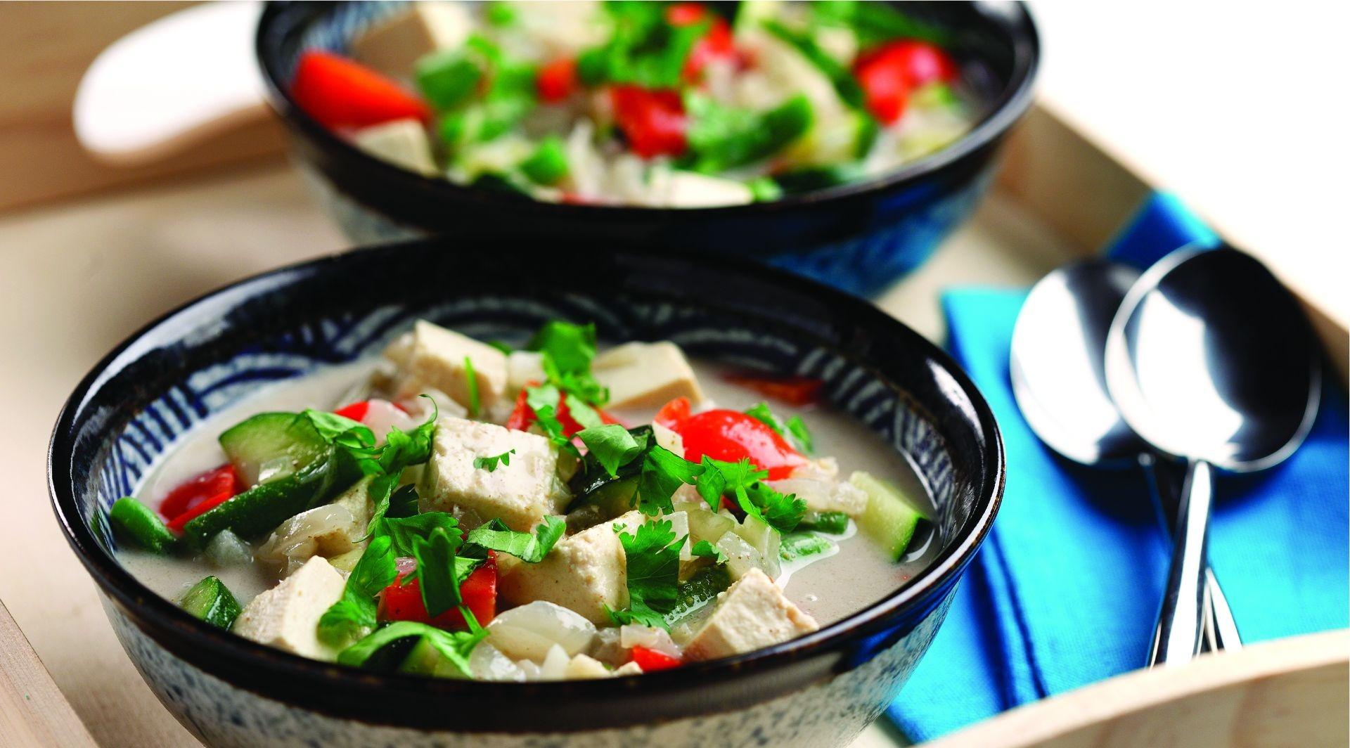 Bols de cubes de tofu, coriandre, poivron rouge, courgette et bouillon