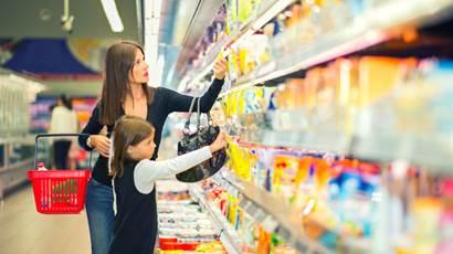 Mère et sa jeune fille font leur épicerie dans l'allée des produits laitiers du supermarché.