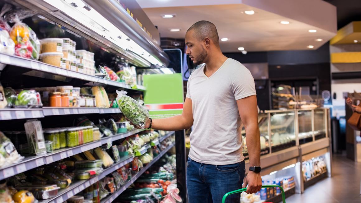 Un homme fait ses courses dans un supermarché.