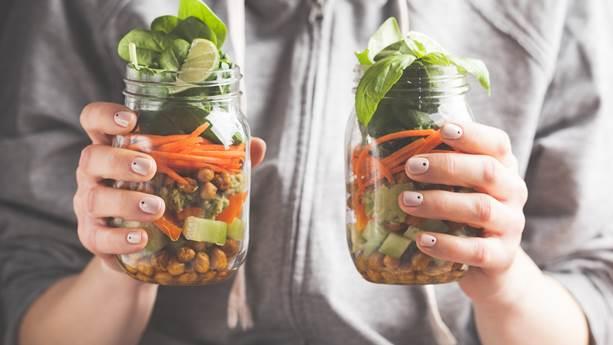 Une femme tient deux salades en pot.